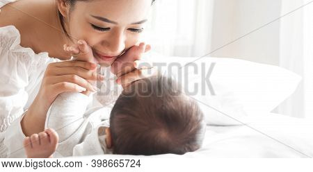 Portrait Of Enjoy Happy Love Family Asian Mother Playing With Adorable Little Asian Baby.mom Touchin