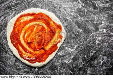 Raw Pizza. Rolled Out Dough With Tomato Paste. On Rustic Background