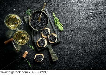 Sandwiches With Black Caviar, Caviar In A Bowl And White Wine. On Black Rustic Background