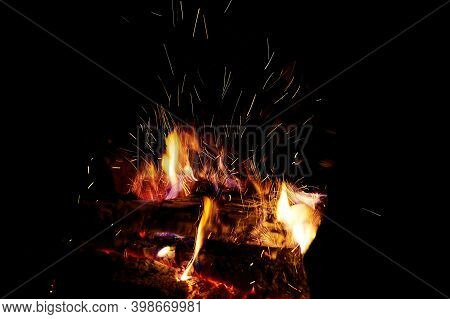 Sparks From Firewood Burning In A Fireplace. Winter Heating At Home. Heat And Energy In Fire