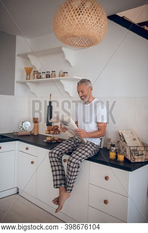 Grey-haired Tall Man Reading A Newspaper In The Kitchen
