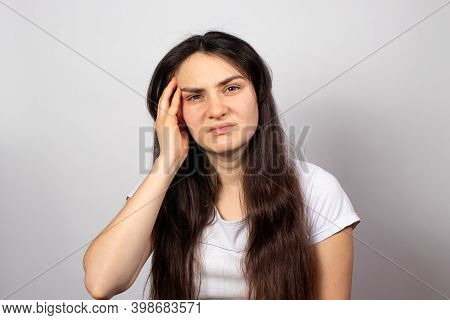 A Tired Woman Holds Her Head With Her Hand, Her Head Hurts. Brain Vascular Spasm, Hypertension, High