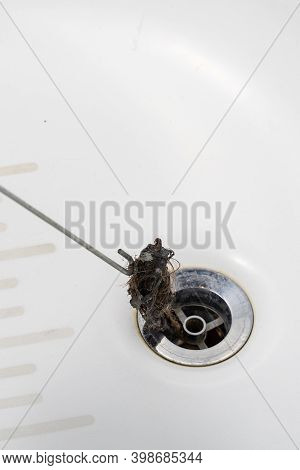 Clogged Drain In The Bathroom. A Plumber Pulls Out A Clot Of Dirt With A Tool