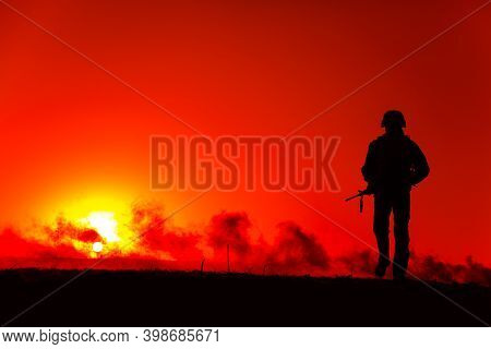 Silhouette Of Army Soldier With Service Rifle Walking To Horizon With Sunset And Smoke. Special Oper