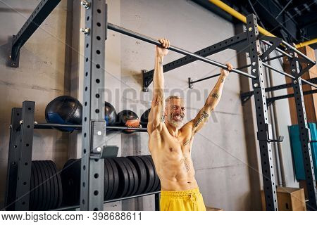 Joyous Sportsman Smiling At The Camera During The Strength Workout