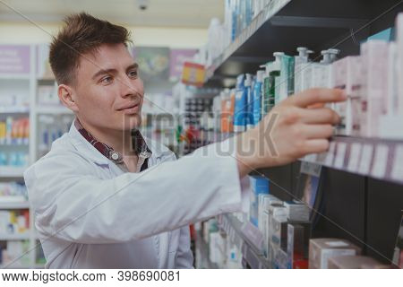 Cheerful Handsome Male Pharmacist Doing Stocktaking, Organizing Products On Shelves At Drugstore. Ch