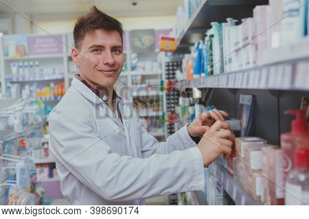 Charming Male Pharmacist Smiling To The Camera, Filling Shelves Of Drugstore With New Products For S