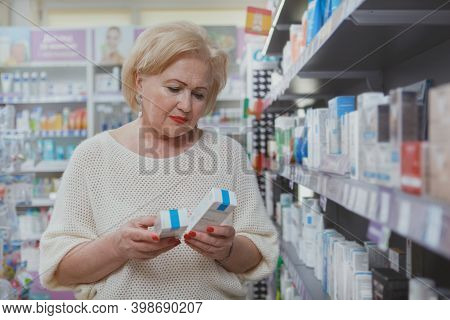 Senior Woman Choosing Between Two Cosmetic Products, Shopping At The Drugstore. Elderly Female Custo