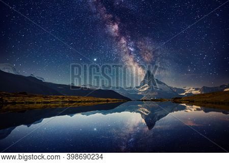 Famous Matterhorn spire under the starry sky. Location Stellisee lake, Cervino peak, Swiss alp, Switzerland, Europe. Photo of popular touristic place. Long exposure shot. Discover the beauty of earth.