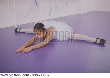 Adorable Little Ballerina Stretching Before Ballet Class At Dance School. Cute Young Girl Exercising