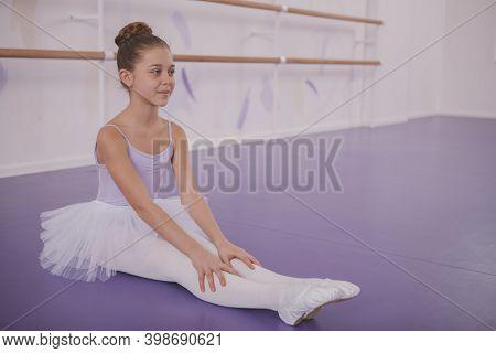 Young Beautiful Ballerina Girl Smiling Joyfully, Sitting On The Floor At Dance Studio. Charming Litt