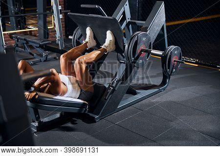 Curly-headed Sportswoman Doing The Incline Leg Press