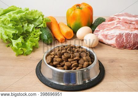 Dry Pet Dog Food With Natural Ingredients. Raw Meat, Vegetables, Eggs And Salad Near Bowl With Dry P