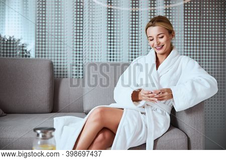 Joyous Woman Reading A Text Message In The Foyer