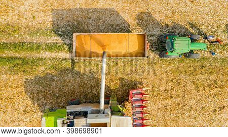 Aerial Top View Of Transshipment From Agricultural Harvester, Combine To The Trailer, Unloading Harv