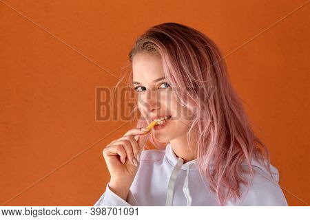 A Young Woman With Pink Hair Eats Fried Potato Slices, French Fries.