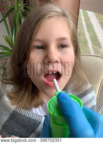 The Child Is Treated With A Throat Spray. Aerosol With An Antibiotic For The Throat In The Hands Of