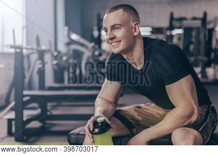 Happy Handsome Young Fitnessman Smiling, Looking Away Joyfully, Resting At The Gym After Workout. Ch