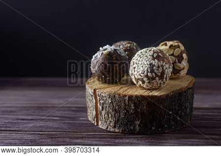 Raw Vegan Dessert Energy Balls Or Raw Vegan Candy With Nuts, Cereals And Dried Fruits On Wooden Back