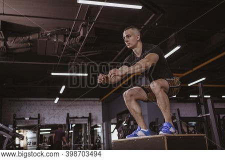 Low Angle Full Length Shot Of A Male  Athlete Box Jumping, Working Out At The Gym. Attractiv