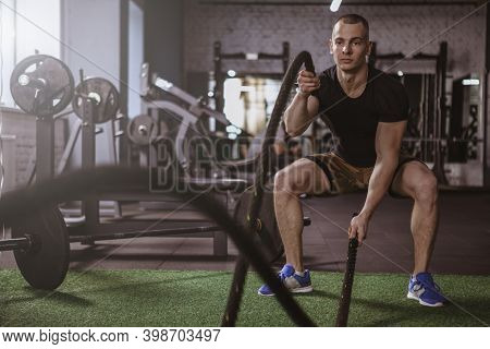 Young Fitness Man Working Out At  Box, Exercising With Battle Ropes. Handsome  Athle