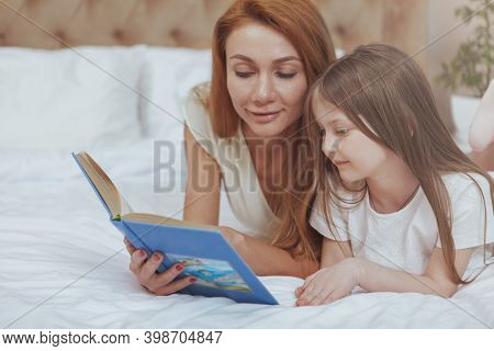 Beautiful Woman Reading A Book To Her Little Daughter. Adorable Little Girl Enjoing Listening To Her