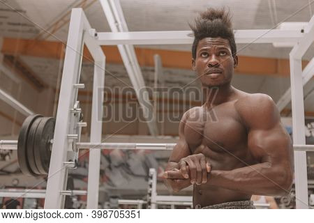 Shirtless African Sportsman With Muscular Strong Body Flexing His Biceps At The Gym. Handsome Athlet