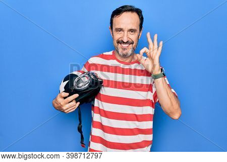 Middle age handsome motorcyclist man holding moto helmet over isolated blue background doing ok sign with fingers, smiling friendly gesturing excellent symbol