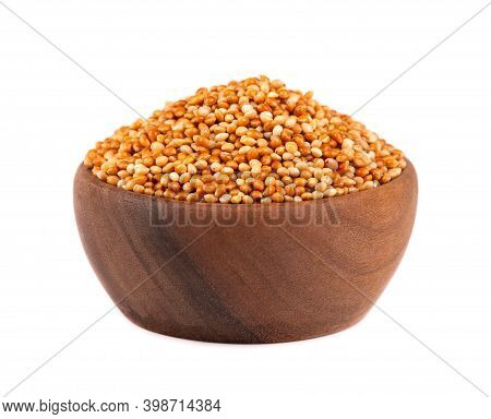 Millet In Wooden Bowl, Isolated On White Background. Unpeeled Millet Seeds.