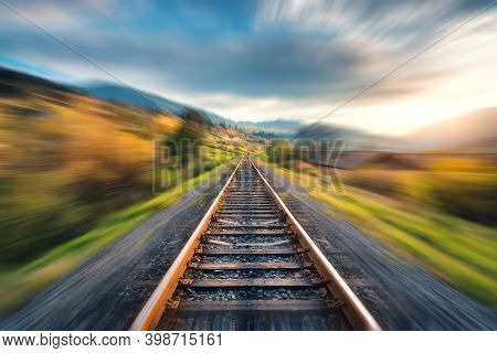 Railroad In Mountains With Motion Blur Effect At Sunset In Autumn. Industrial Landscape With Railway
