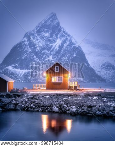 Alone Rorbu On Sea Coast And Snow Covered Mountain At Night In Winter. Lofoten Islands, Norway. Land