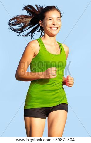 Running woman. Happy, young and athletic female fitness model in sports wear jogging outside.