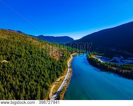 Highway Running Through A River Valley In The Mountains With Pristine Clear Blue Water And Frozen Pl