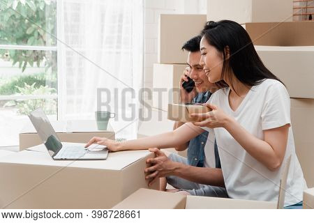 Smiling Young Asian Happy Couple Use Laptop For Home Decoration Ideas At Moving Day In Their New Hom