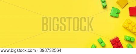 Multicolored Plastic Kids Constructor On Yellow Background. Colored Childrens Bricks For Constructio