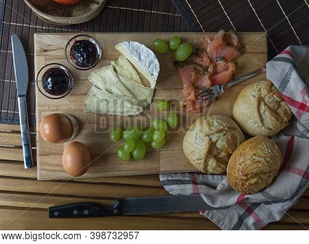 A Tasty European Breakfast With Eggs, Salmon, Grapes, Cheese And Rolls Topview