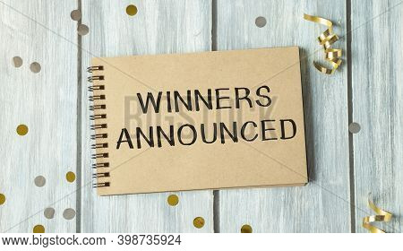 Blank Notebook Isolated On Wooden Background . Whith Text Winners Announced