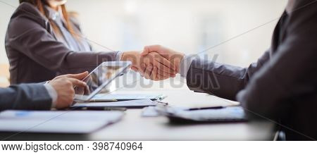 Handshake Of Business People At The Negotiating Table. Close Up.