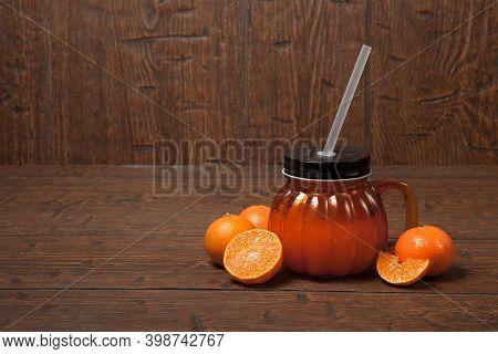 Glass Jar Of Fresh Orange Juice With Slice Of Tangerine Or Mandarin Orange Fruit On Old Wooden Table
