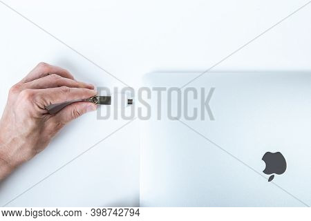 Belarus, Minsk - July 13, 2020: Apple Inc. Product Design Space Gray Macbook Pro. Man Inserting A Fl