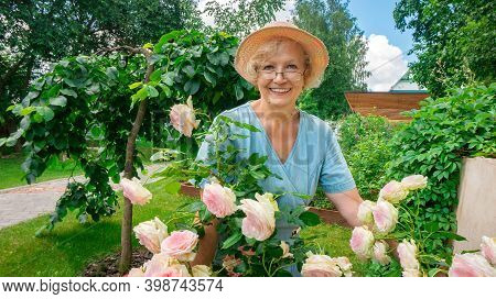 Gardening As A Retirement Hobby. Portrait Of An Attractive Woman Gardener In Glasses And A Hat Near