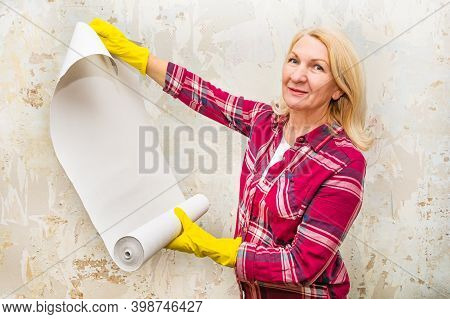 Woman Holds Wallpaper In Her Hands. Happy Blonde Is Preparing To Repair. Wallpaper For Painting. Diy