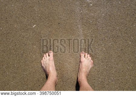 Man's Feet From Top And Sea Sand. Travel Scene And Background