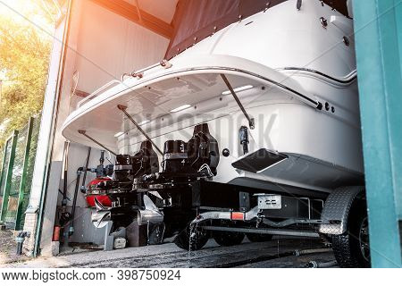 Big Luxury Cabin Motorboat Cruiser Yacht Engine At Trailer Ramp From Storage Boat Hangar Garage. Shi