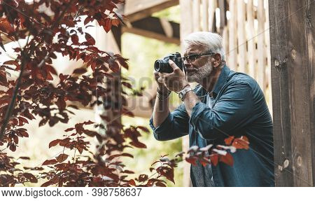 A Mature Man With A Beard And A Camera Takes Pictures, Paparazzi. Retired Active Hobby, Senior Journ