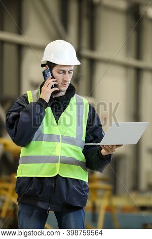 Portrait Of A Man , Factory Engineer In Work Clothes Holding Laptop And Phone, Controlling The Work