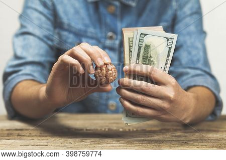 Hands Hold Money And A Brain. Making Money With Your Intellect. Investing Money In Education.