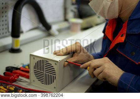 Assembly Of The Air Purifier.an Employee Repairs Air Conditioners And Air Purifiers.