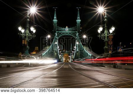 A Picture Of The Liberty Bridge In Budapest, Hungary At Night With The Light Traces From The Cars.