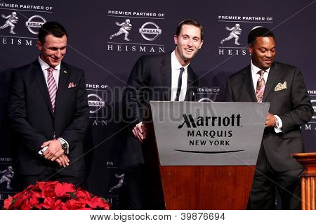 NEW YORK-DEC 8: Texas A&M quarterback Johnny Manziel, offensive coach Kliff Kingsbury & head coach Kevin Sumlin with 2012 Heisman trophy at the Marriott Marquis on December 8, 2012 in New York City.